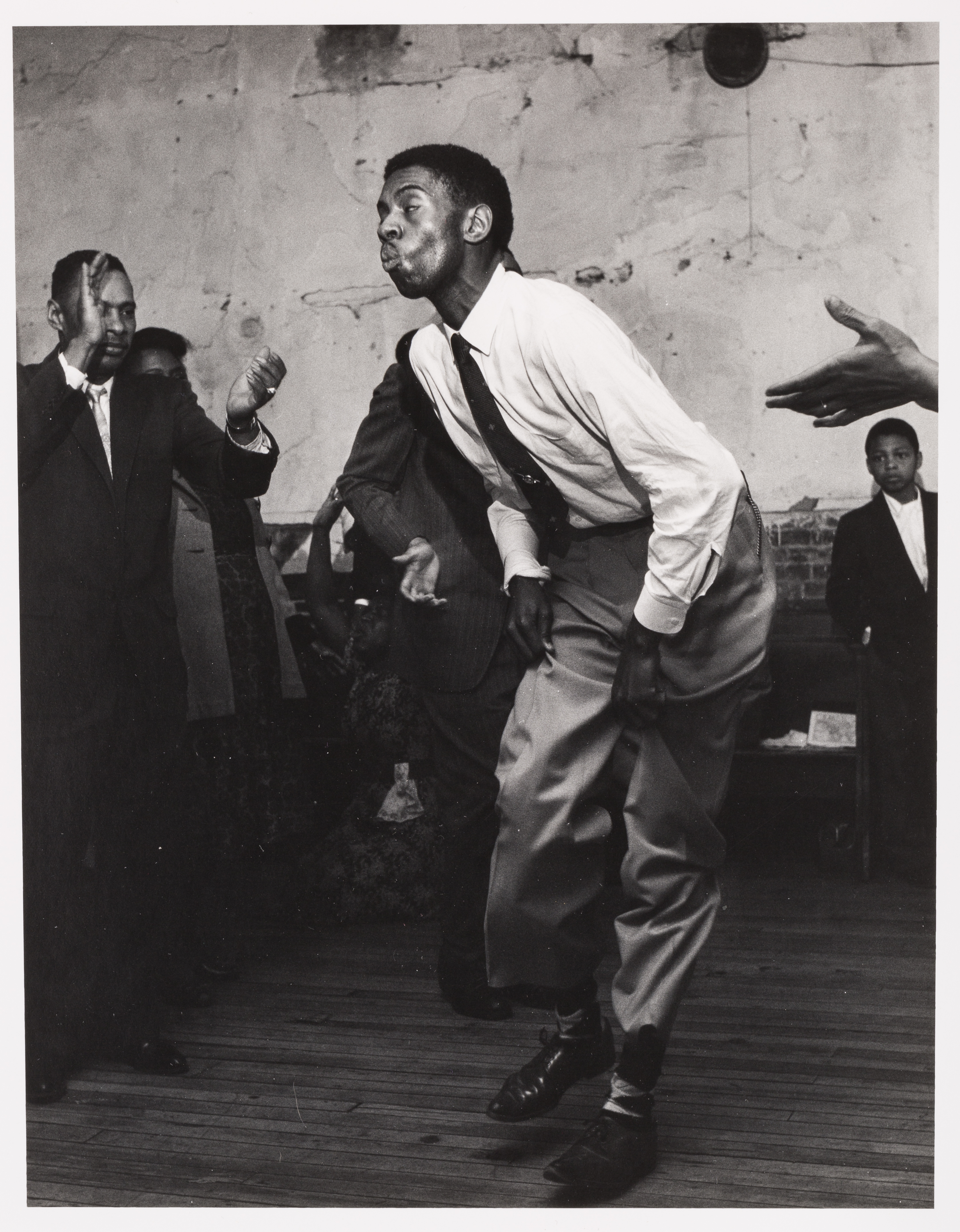 Black-and-white photo of an African-American man dancing and people around him clapping