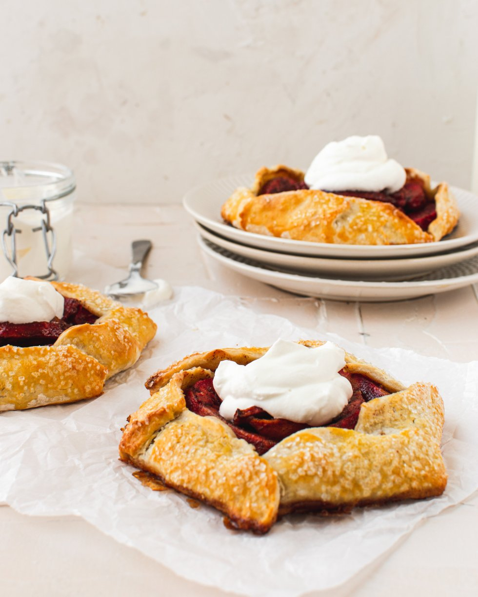 Three easy apple galettes are topped with whipped cream.