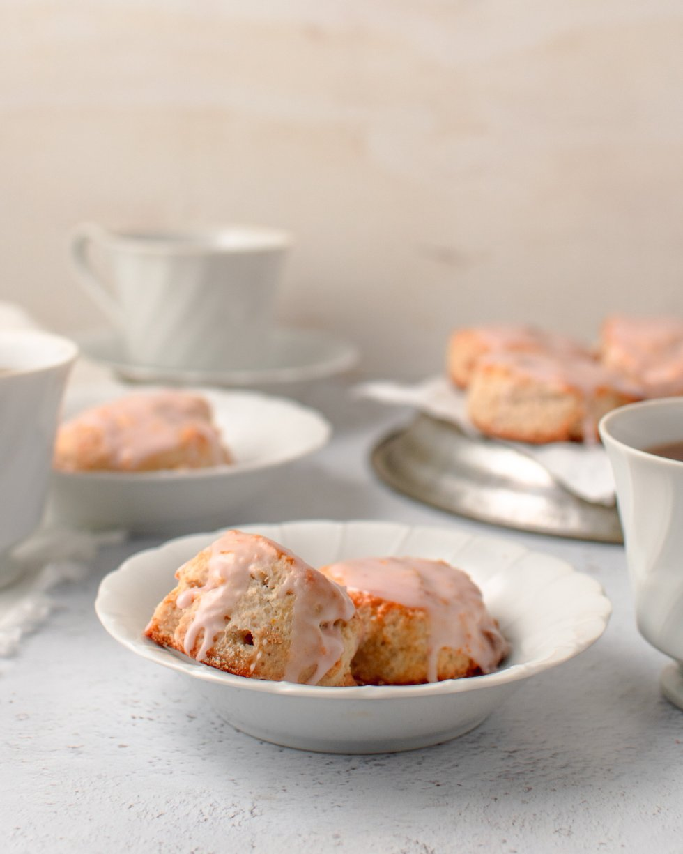 Blood orange scones with white chocolate chips covered in blood orange glaze sit in a bowl next to a cup of cofee