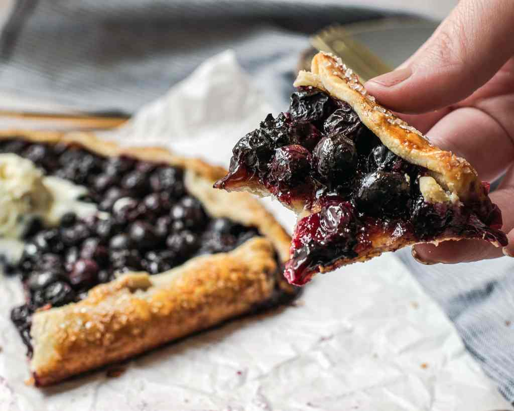 Bite out of slice shows how the blueberries have maintained their texture in baking