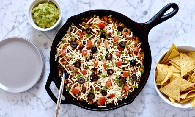 Sofritas Skillet Dip Recipe - This is a copycat of the vegan option at Chipotle that's been turned into a dip loaded with dairy free nacho cheese, and topped with fresh veggies like tomatoes, green onions and olives. It's super flavorful and perfect for game day or as a weeknight meal.