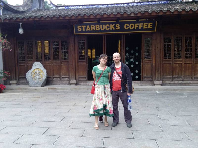 Starbucks coffee shop, Chinese style wooden architecture, Chris and Ola standing outside