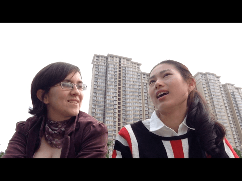 Two women talking with buildings in the background