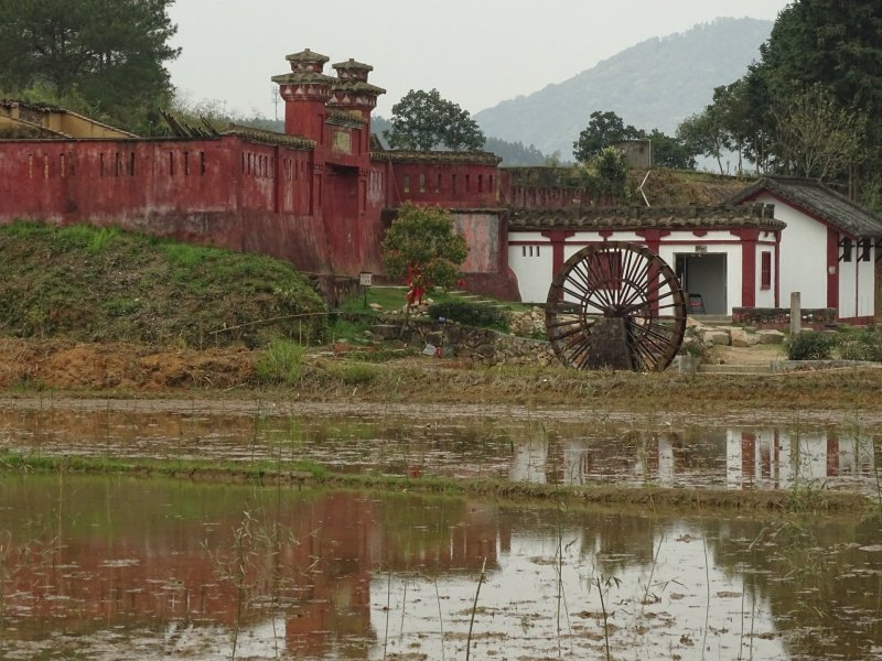 An ancient red wall on the left marks the entrance to the MinYue ruins