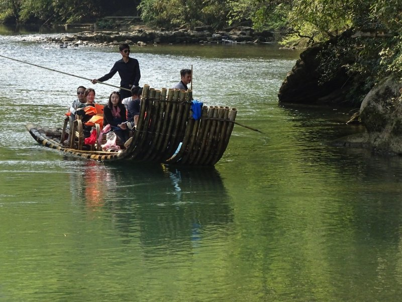 A bamboo raft with Chinese family and oarsmen