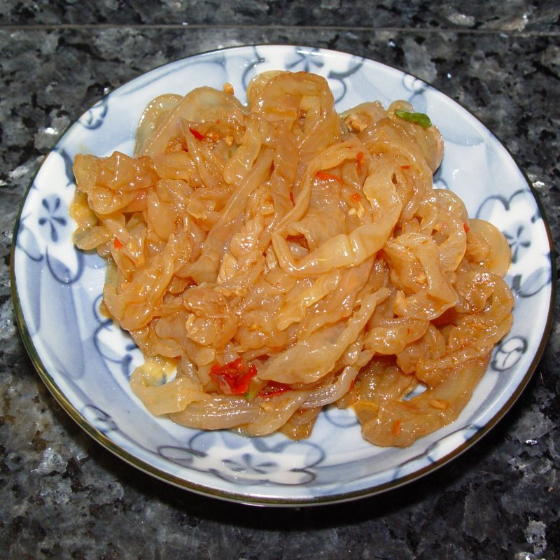 Jellyfish served on a plate, pickled with sesame oil and chili sauce
