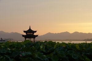 Pagoda with sunset and silhouette of mountains in background