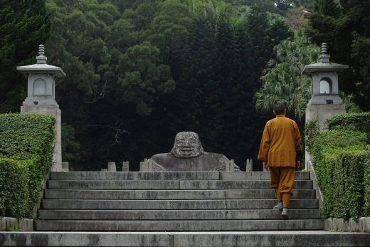 Monk in yellow habit walking up steps towards Mi Le Fo (Laughing Buddha)