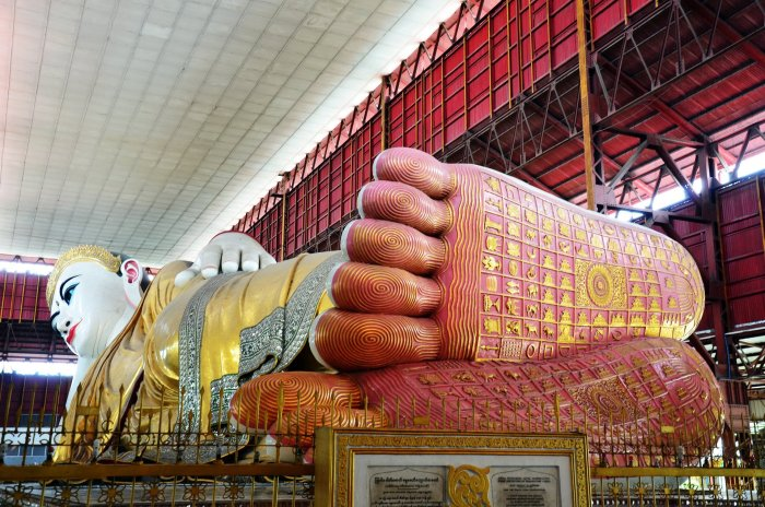 Chaukhtatgyi Paya reclining Buddha. Her red feet are closest to the camera and there's some golden symbols (maybe Chinese Oracle script) on the feet.