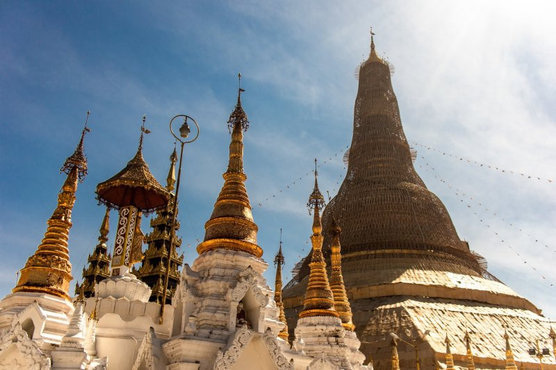 View looking up at Shwedagon Paya stupa, with smaller marble and gold pagodas in foreground.