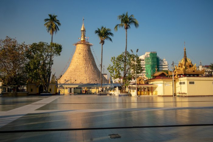 Botaung Paya main stupa from a distance, flanked by palm trees.