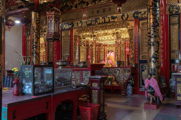 Inside Kheng Hock Keong temple. Everything's red and wooden, as you see in  traditional Chinese temples. The altar is framed with gold.
