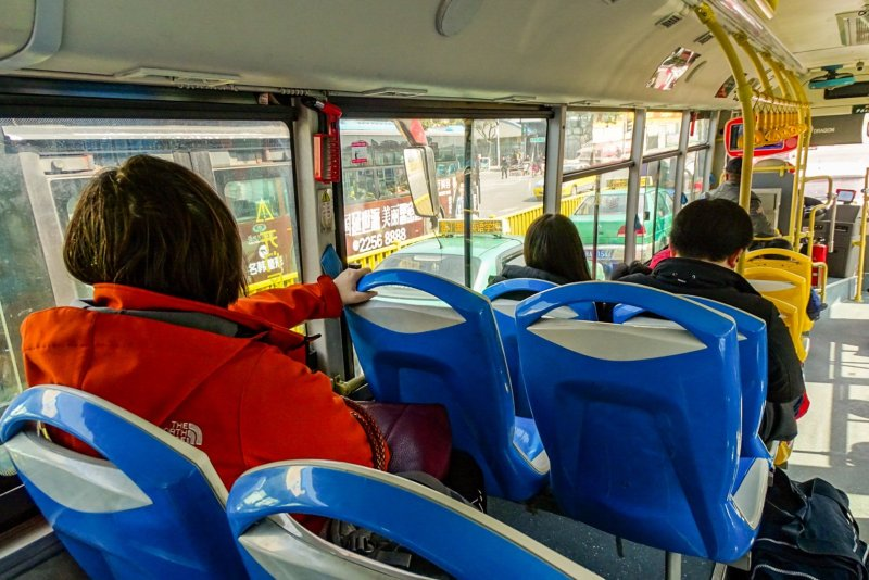The inside of a Chinese bus. Ola is sitting in an orange windbreaker at the back, her back turned to the camera.