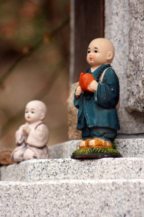 A porcelain statue of a Buddhist standing on some kind of stone pagoda.