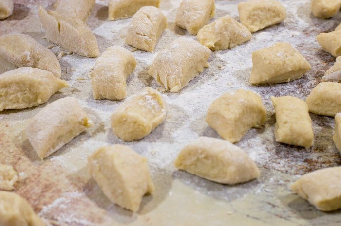 Potato dumplings arranged on a table and dusted with flour