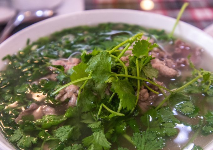 A bowl of traditional Hanoi pho, garnished with spring onions and coriander