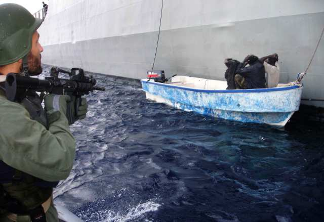 in this Greek navy handout photo released on Wednesday, April 1, 2009, a navy commando is seen detaining a speedboat with suspected Somali pirates tied up alongside a Greek frigate in the Gulf of Aden after a failed attack on a Norwegian cargo ship. The navy said Greek commandos later released the five men after no arms were found on the vessel. Nobody was hurt in Wednesday's pirate attack, which the Norwegian Sigloo Tor's crew fought off with fire hoses. (AP Photo/ Greek Navy, HO )  **  EDITORIAL USE ONLY  **