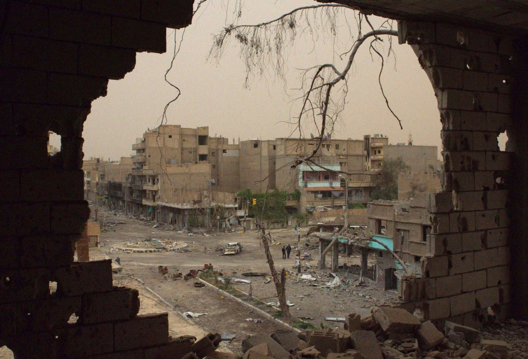 People walking down a street are pictured through a hole in a building in Deir al-Zor April 4, 2013. Picture taken April 4, 2013. REUTERS/ Khalil Ashawi (SYRIA - Tags: CONFLICT TPX IMAGES OF THE DAY)