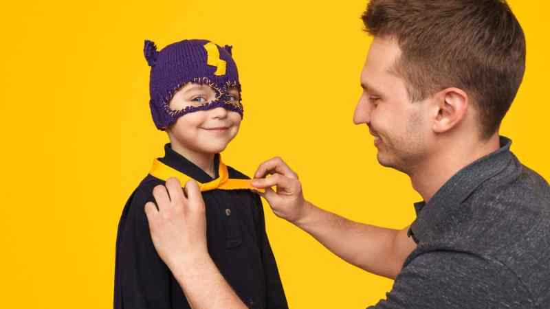 A Father helping his kid wear a personalized superhero cape