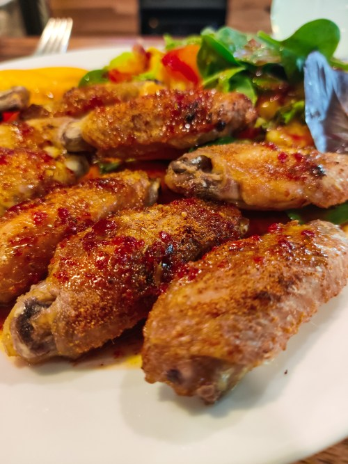 A close up shot of crispy chicken wings on a white plate with Honey Aleppo sauce drizzled on the wings. Some salad is poking up from behind the wings on the back end of the plate.
