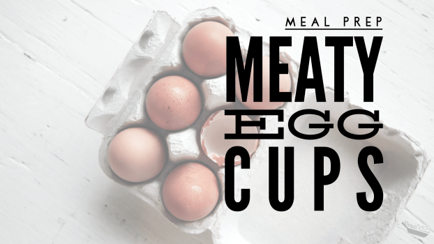 """A lowered opacity overhead shot of a six-egg egg carton featuring five whole brown eggs and half the shell of a sixth egg. Text overlay reads """"Meal Prep Meaty Egg Cups"""""""