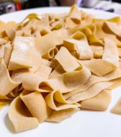 A close up shot of the fresh pappardelle we made. It is not yet cooked and you can still see some of the flour on the raw noodle dough.