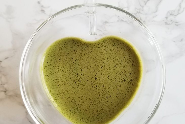 An overhead shot of a matcha latte in a clear glass heart-shaped mug on a white marble background.