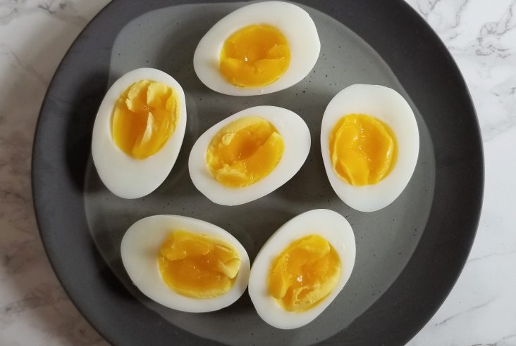 An overhead shot of six egg halves with yolks exposed sitting on a gray textured plate on a white marble background.