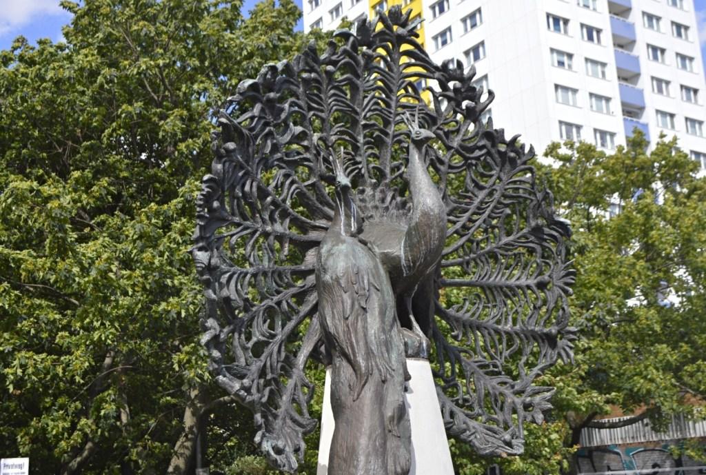 Pfauenbrunnen der berliner Künstlerin Margit Schötschel-Gabriel - Bronze & Eisen auf Naturstein Skulptur Springbrunnen Neubaugebiet Holzmarktstraße und Alexanderstraße Berlin be kitschig blog