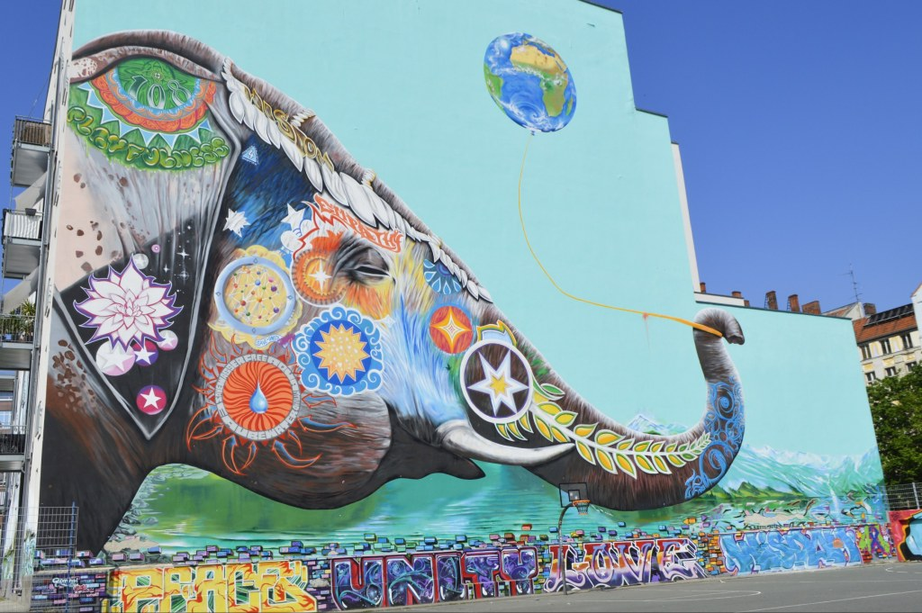 ! by Jadore Tong - Huge elephant mural holding the world as a ballon - street art off Friedrichstraße Berlin  bekitschig.blog street art postcards from Berlin #22