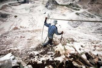 Seorang penambang kapur sedang mencari posisi yang tepat untuk menambang di tebing curam hanya dengan pengamanan tali tambang (JP/Wendra Ajistyatama)