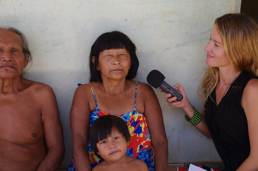 An elderly, indigenous woman with black and straight hair and bangs, she is wearing a colorful dress and looking at the camera. On her lap, there is indigenous boy without shirt. On the left side of the picture, an old man, with white hair and no shirt. Both are sat, their backs are against the white wall, and they're looking at the camera. On the right side of the image, there is a white woman, with long blond and wavy hair, she is sitting sideways to the camera and looking at the couple of natives. She holds a microphone with her right hand.