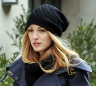 "Blake Lively looking all too chic in a cinched navy trenchcoat, beanie, and knee length boots - looks like the ""Gossip Girl"" star is filming a hide-and-seek scene too as she dodges behind a corner, peeking out!"