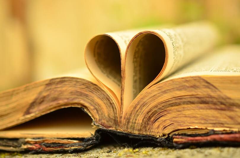 nyitott könyv, melynek meghajtott lapjai szívet formálnak