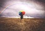 lány színes esernyővel áll az esőben és szivárványt néz