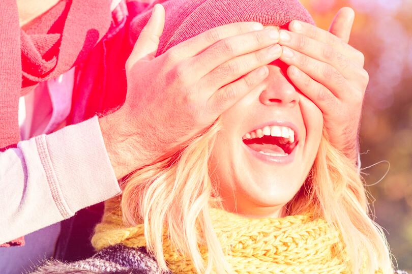 mosolygós lány, akinek befogják a szemét