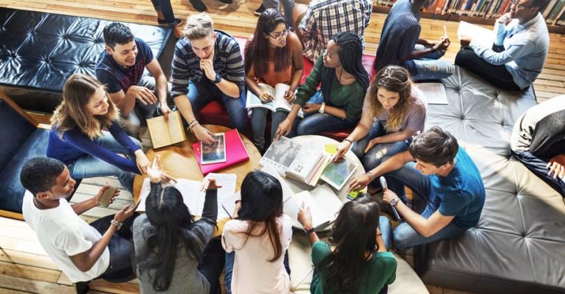 fiatalok egy asztal körül együtt dolgoznak