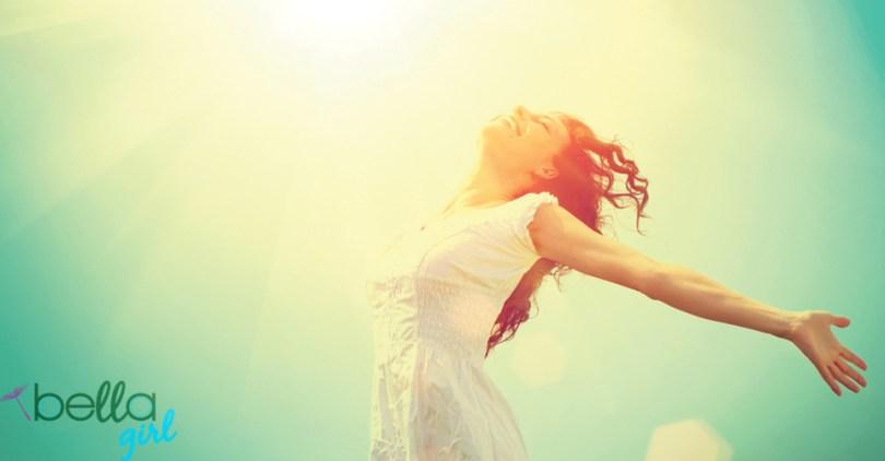 fiatal nő kitárt kezekkel a napfényben