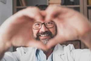 Close up portrait of smiling young caucasian male nurse or GP in white uniform show heart love