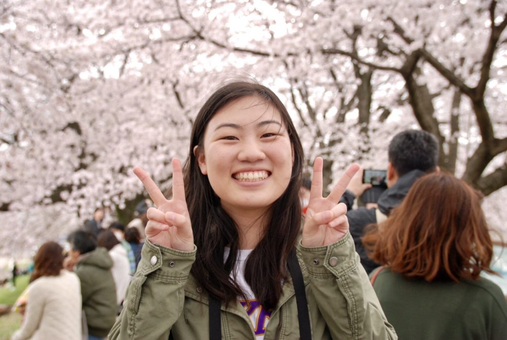 Veronica Rose Tan smiling and giving peace sign in front of cherry blossom trees