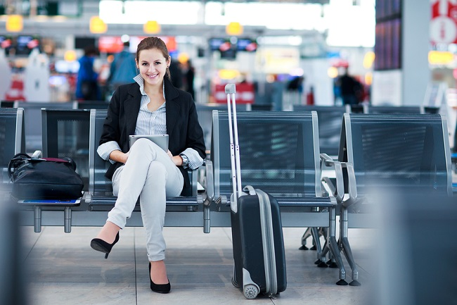 young-female-business-woman-at-airport-using-tablet-pc