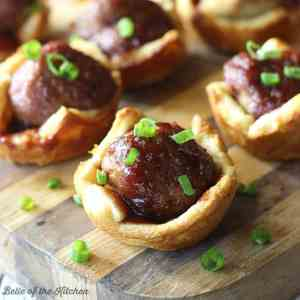 Meatballs topped with a tangy sauce and baked inside a flaky crescent crust. This quick and easy appetizer is sure to please this holiday season!