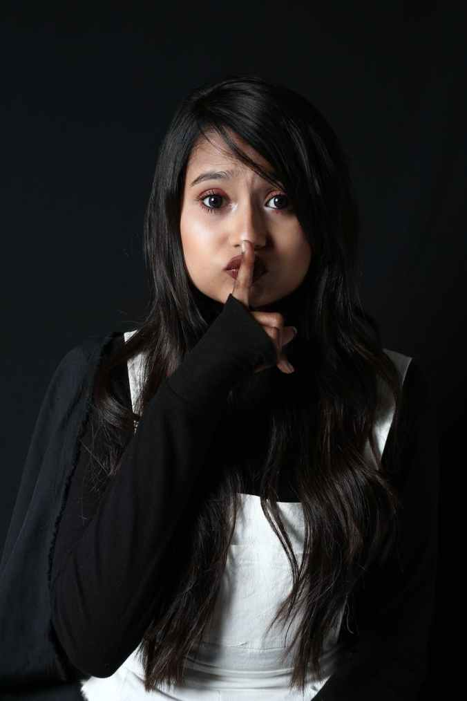 young woman showing keep silence gesture