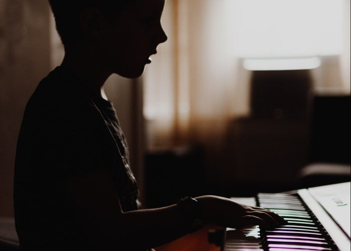Boy playing piano in room