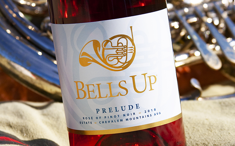 Bottle of pink wine in front of close up of French Horn