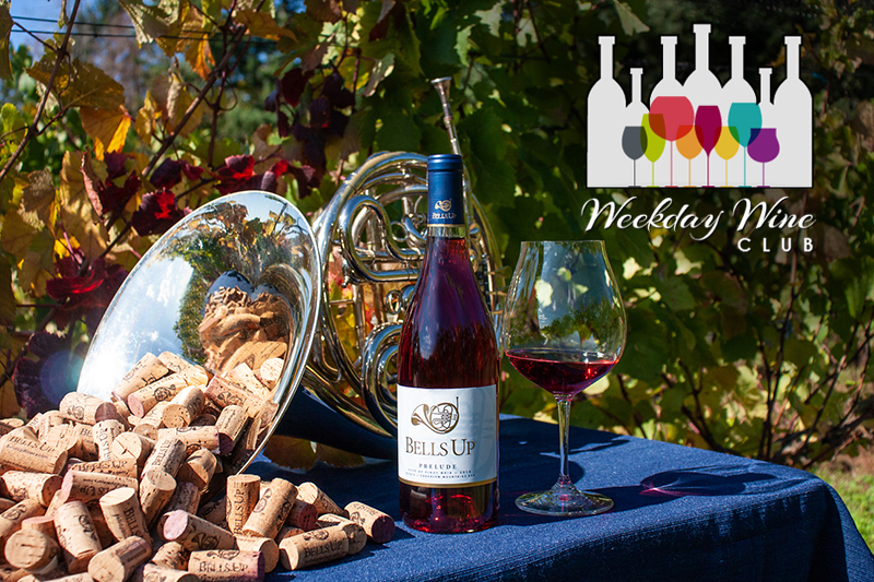 Photo of a french horn with corks spilling out of the bell with a bottle and glass of pink wine