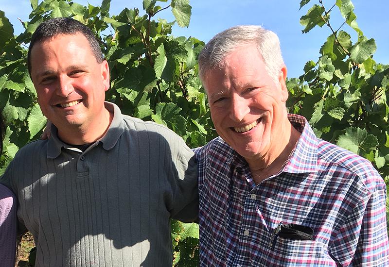 Two men smiling in a vineyard