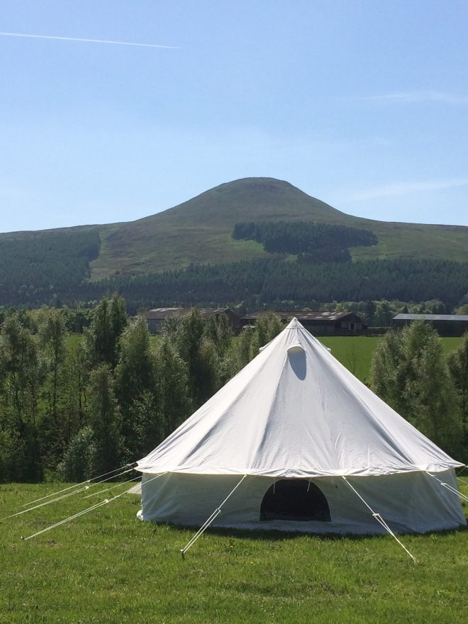 View of hill in background and bell tent in foreground
