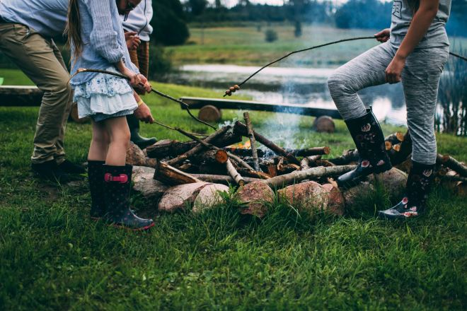 Roasting marshmallows over an open campfire, first family camping trip. Photo by Daiga Ellaby on Unsplash