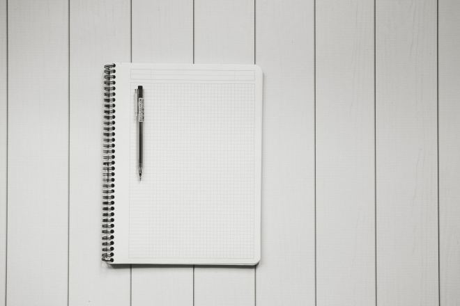 Spiral notebook with pen, for making list for first family camping trip. Photo by Kelly Sikkema on Unsplash